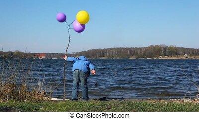 boy on coast with balloons - boy on coast near young tree...