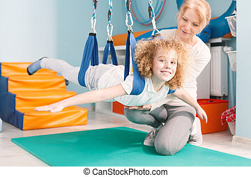 Boy on dual swing - Therapist and happy boy on dual swing