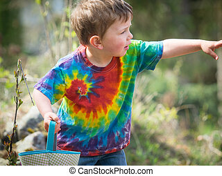 Boy on Easter Egg Hunt - Cute boy in tie dye shirt on Easter...
