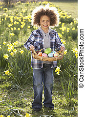 Boy On Easter Egg Hunt In Daffodil Field