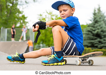 Boy on Skateboard Adjusting Elbow Pad in Park - Full Length...