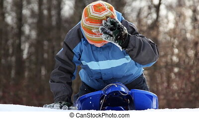 boy on sled pushes his hands and ride down snow mountain