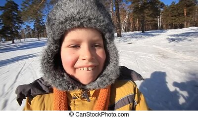 A little boy driving in a sledge
