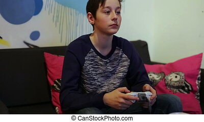 Boy on Sofa Playing in Computer Game with Joystick -...