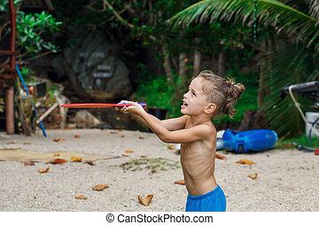 boy on the beach playing beach tennis