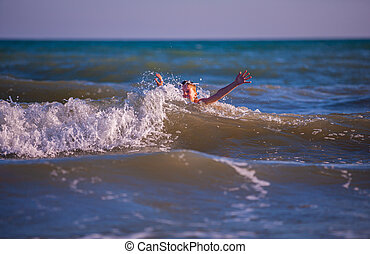 Boy on the beach, playing with the waves, summer time