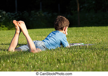 Boy on the grass - A boy lying on the grass reading a...