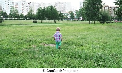 Boy on the lawn running away from mom