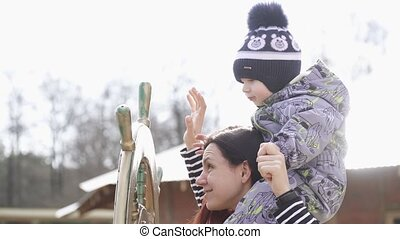 Boy on the shoulders of mom turns