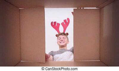 Boy opening cardboard box - Young happy teen boy with ...