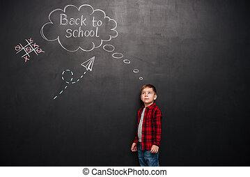 Boy over chalkboard with school drawings while looking on it