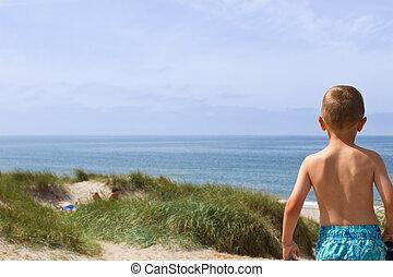 Boy overlooking the North Sea coastline - Young boy is...