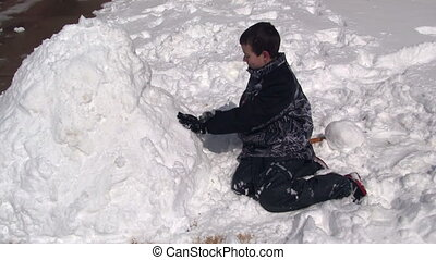 Boy packing snow for snowman