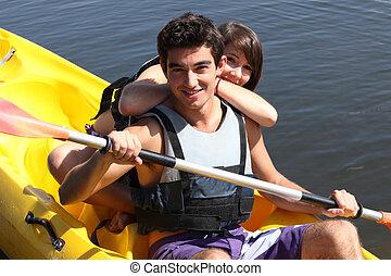 Boy paddling in canoe