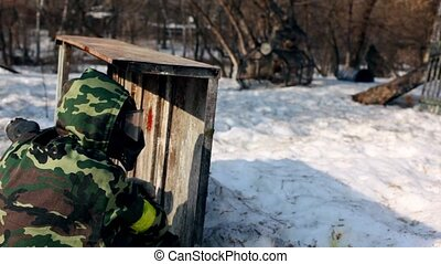 Boy paintball player sit in ambush behind fence and then run away