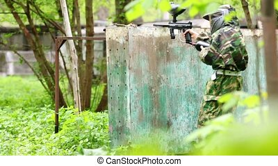 Boy paintball player sits in ambush behind metal fence, then stands up and runs away