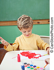 Boy Painting With Watercolors In Art Class