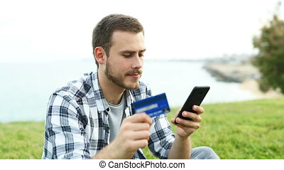 Boy paying with credit card and phone outdoors - Happy boy...