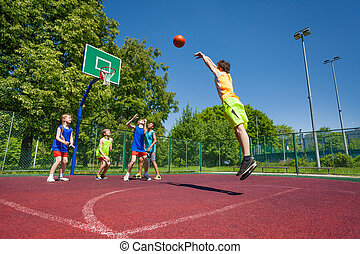 Boy performs foul shot at basketball game on the playground ...