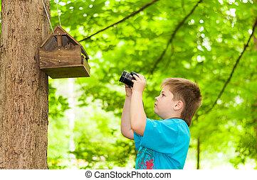 Boy photographing a bird feeder