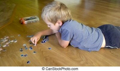 boy plaing with puzzle on the floor