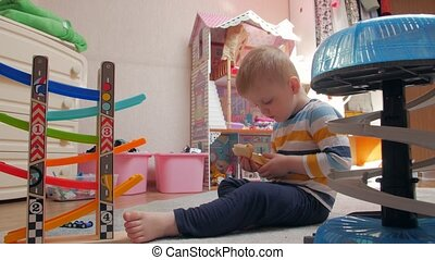 Boy play and chews sandwich childrens room home interior