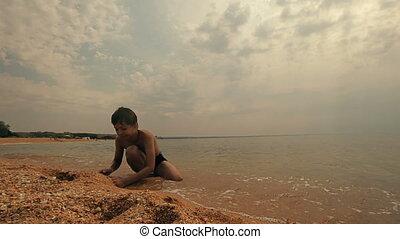 Boy play with sand on beach slowmo