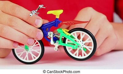 Boy play with toy bike, rotates pedals with rare wheel