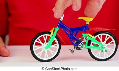 Boy play with toy bike, rotates handlebars, try to make...