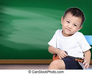 Boy playin ukulele guitar with green chalk board background