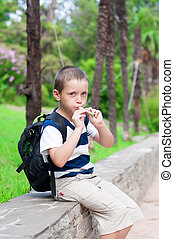 boy playing a pipe in nature