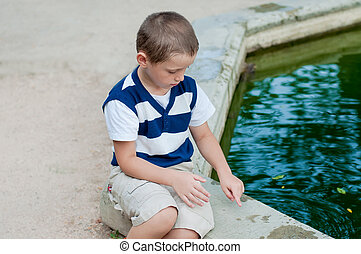 boy playing by the fountain