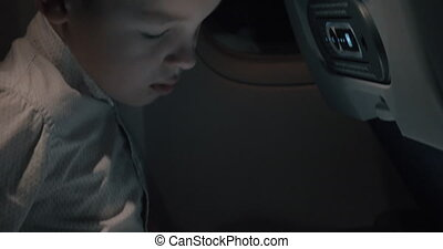 Boy playing chess on touch pad during night flight