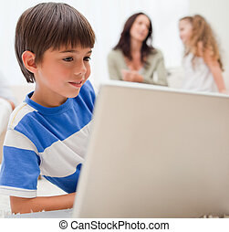 Boy playing computer games with his family behind him -...
