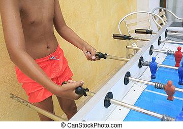 Boy playing  foosball in a pool