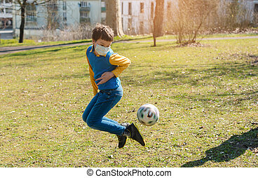 Boy playing football in the park despite the Covid-19 crisis