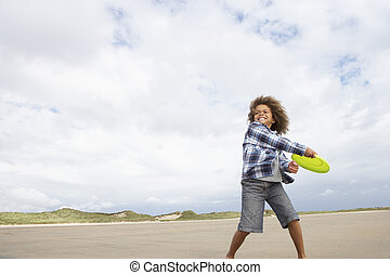 Boy playing frisbee on beach