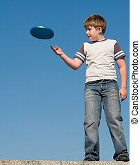 boy playing frisbee