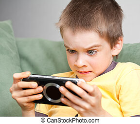Boy playing game console - Young boy playing handheld game ...