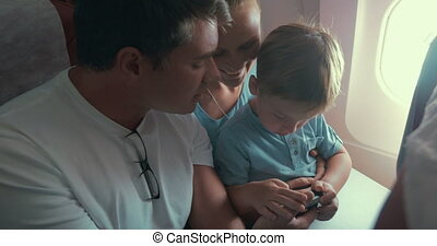 Boy Playing Games in Smartphone, Parents by Him