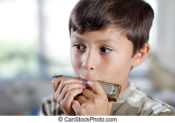A young musician practices his harmonica in his bedroom with shallow depth of field - copy space to left