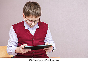 boy playing in a tablet at school