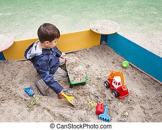 boy playing in sandbox - Cute boy in jacket playing in...