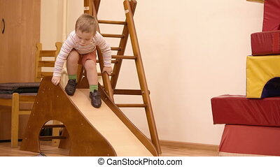 Boy playing in the nursery. - Little boy running down from a...