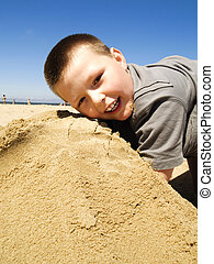 boy playing in the sand on the beach