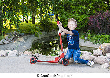 Boy playing on his scooter in the local park.