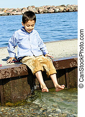 Boy playing on pier - Portrait of young boy dipping feet in...