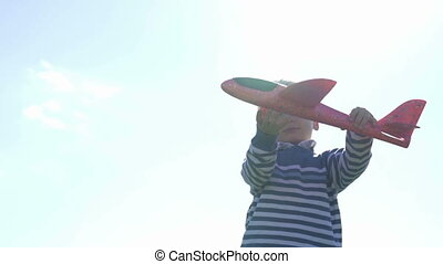 Boy playing outside with toy airplane slow motion