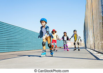 Boy playing roller skates with friends outdoors