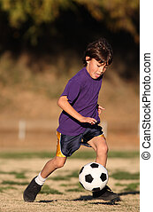 Boy playing soccer in late afternoon light